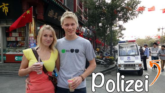 Reise durch China: Polizei in China ist nicht immer ein leichtes Thema.. Gina und Kilian mit Polizeiauto im Hintergrund